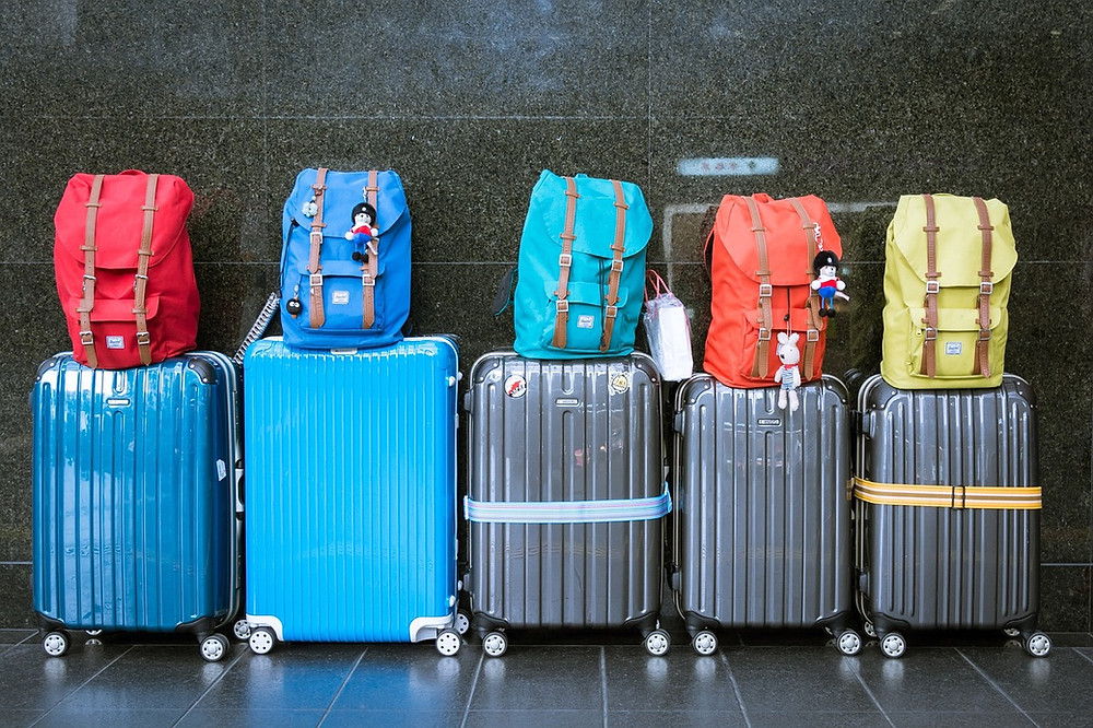 Suitcases and bags lines up in a row at an airport