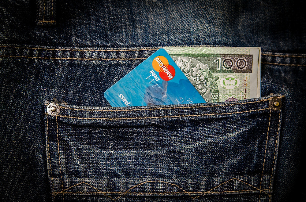 cash and a credit card in a jean pocket