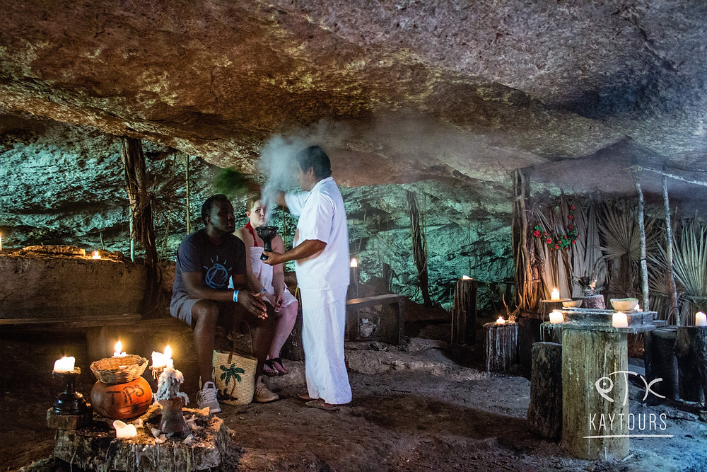 people taking part in a mayan ceremony with a shaman in a cenote.