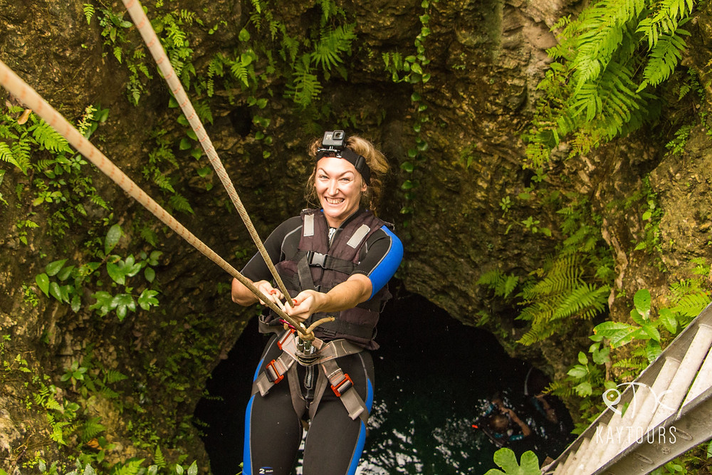 a happy guest rappelling in to a cenote on our Mayan Explorer Tour