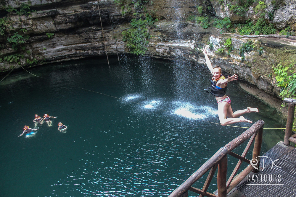 Picture of a woman jumping into a cenote
