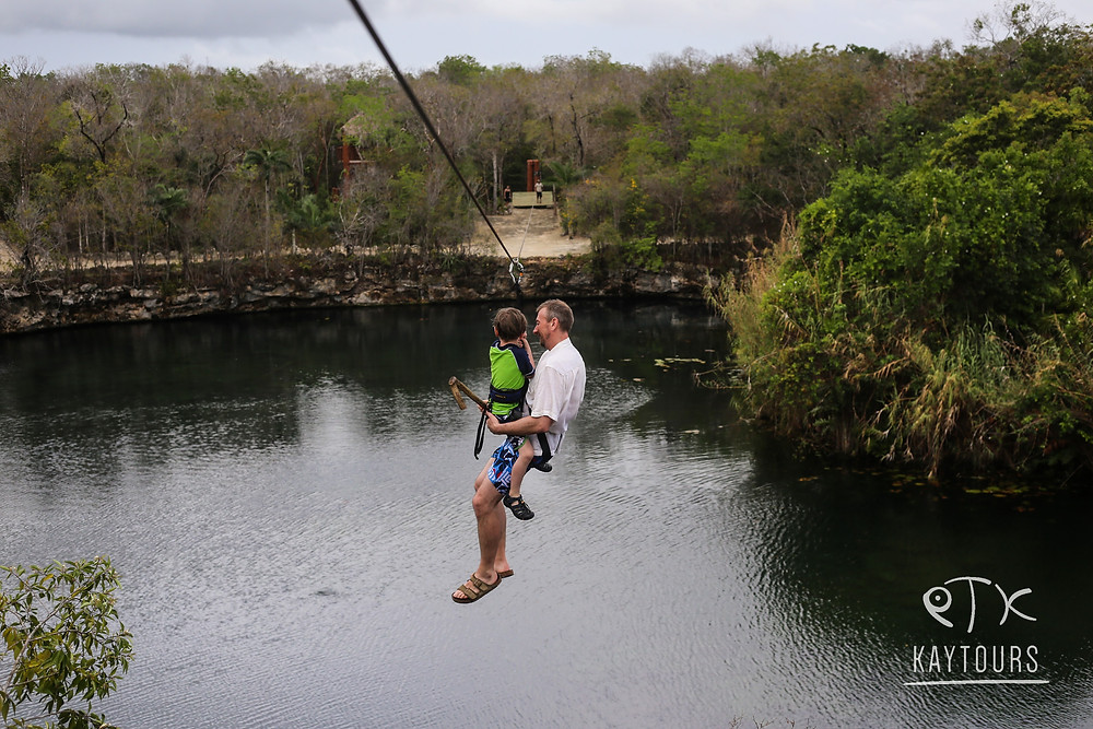 a father and son zip lining across a cenote