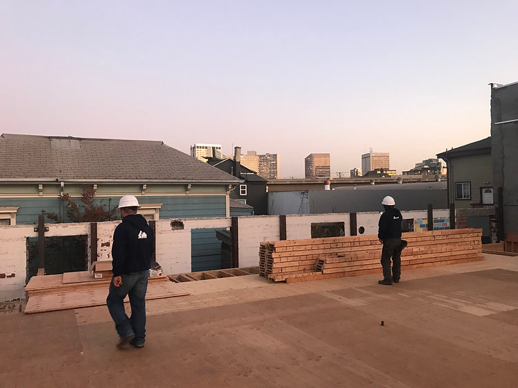 Framers inspecting received material on the roof. The sky during a bay area sunset is displayed in the background.