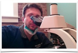 Dr. Stein visualizing histopathology slides over the microscope. Mohs surgery is performed on-sit at Stein Dermatology in San Diego.