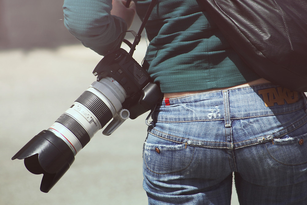Female photographer with DSLR camera with long lens.