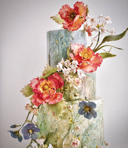 Watercolour impressionist wildflower meadow cake with sugar poppies, flax flowers, clover & agapanthus