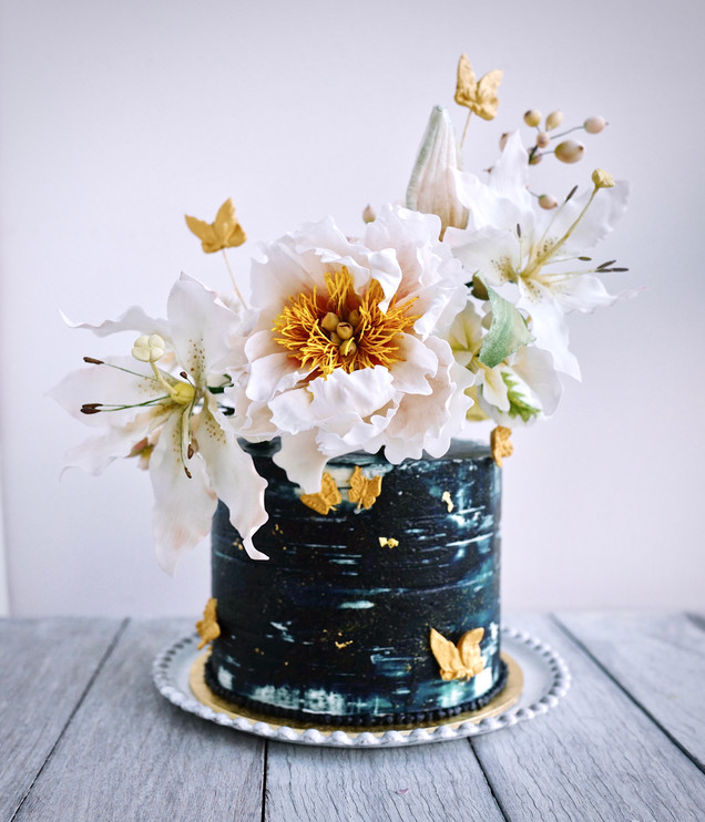 A striking cake in navy, white & gold with handcrafted sugar peony, lilies & gold leaf & butterflies