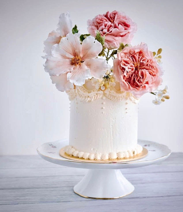Sugar David Austin roses and large cosmos flowers jostling to be the center of attention on this cake with classic buttercream piping details