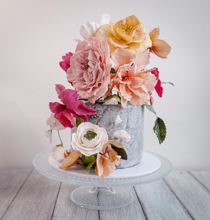 Cascading bouquet of roses, orchids, sweet pea, ranunculus on textured fondant base