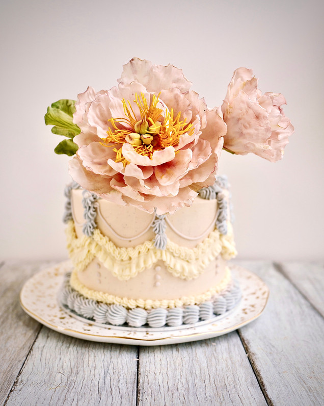 Delicate pale pink sugar peonies dress up vintage inspired buttercream piping even further..
