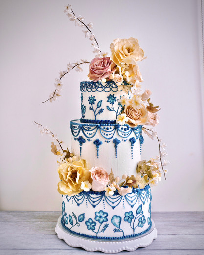 A delftware inspired 3-tier buttercream cake decorated with a flowing medley of wild roses, classic roses, garden tea roses, hypericum berries & blossom branches