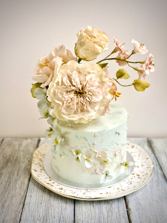 Ornate yet contemporary - Sugar roses, lisanthus & cherry blossoms ascend out of a turquoise coloured cake with abstract petals.