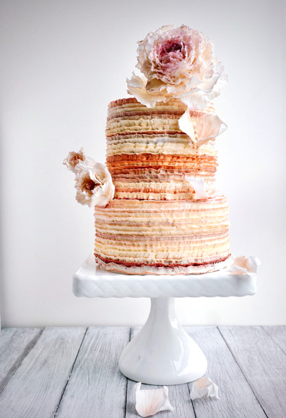 The perfect cake for lovers of frilly things - buttercream ombre frills in ochre colors with the ultimate ruffled statement peonies