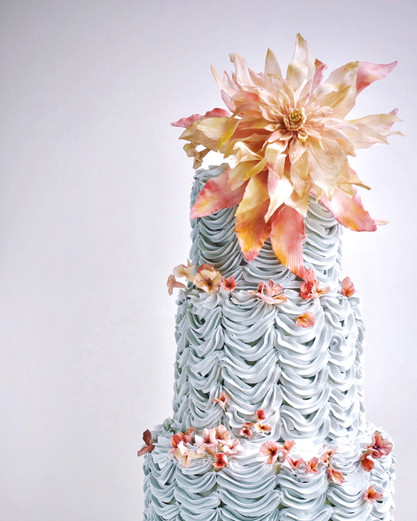 A showstopping dahlia sits atop a lavishly ruffled buttercream cake