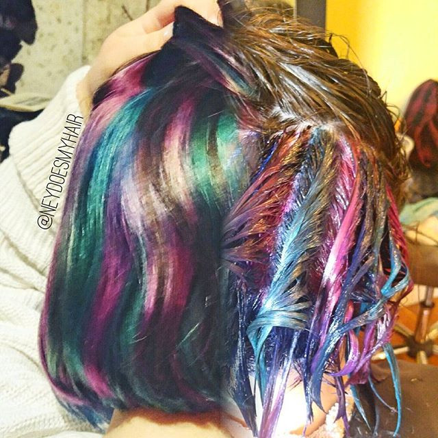 brightly colored pink green and blue hair with one side dried and the other processing.