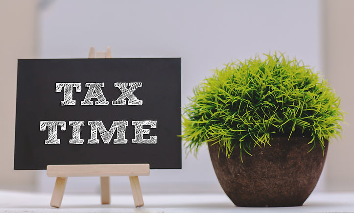 TAX TIME written on chalkboard with gree