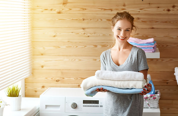 a Happy housewife woman in laundry room with washing machine  _.jpg