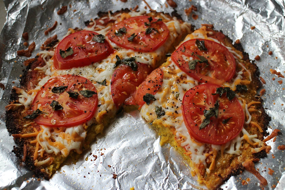 cauliflower pizza with a slice gone, eaten by Rose Moran the Health Coach, Yoga Instructor and Ball Therapy Instructor