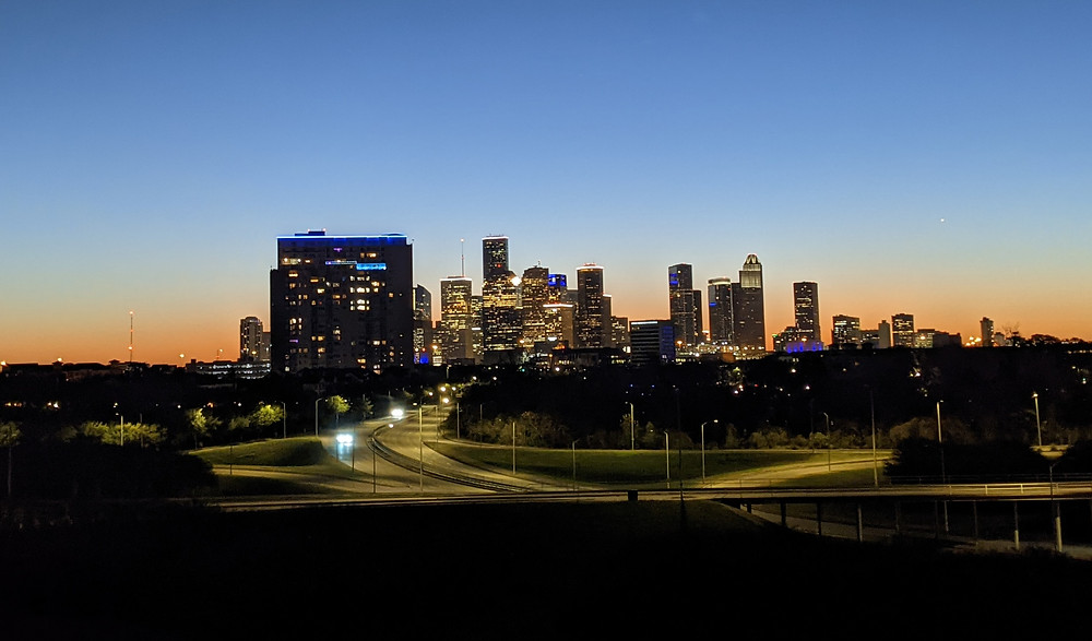 The skyline of Houston at dawn. The sky is colored orange and blue. Headlights of a few cars light up the network of roads in the foreground.