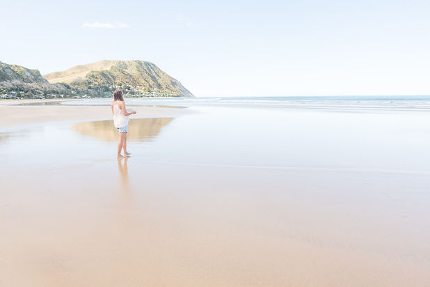 Female artist carrying paper towards the ocean on a New Zealand beach, Makorori Beach, Gisborne, New Zealand, Hills in New Zealand