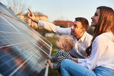 Man shows his family the solar panels on the plot near the house during a warm day. Young