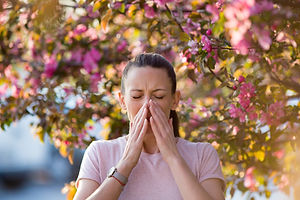 Young pretty woman sneezing in front of blooming tree. Spring allergy concept.jpg