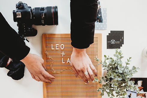 LEO + LAINE Creative Marketing Agency_Hands placing a necklace on a letterboard_Camera, business cards, and a plant