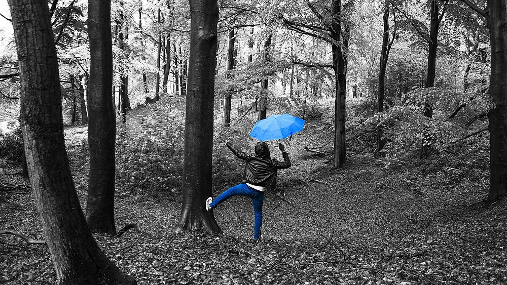Person in dark woods, dancing, blue umbrella