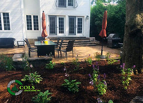Backyard stone patio design & garden beds installation