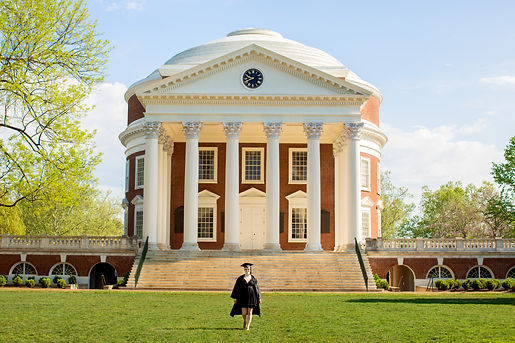Lucy Trieshmann wearing a graduation cap and gown, walking away from the UVA Rotunda.