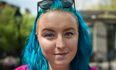 Headshot of Lucy with blue hair, sunglasses, and a pink dress.
