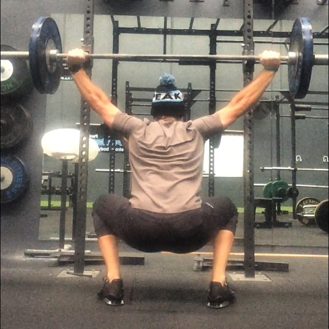 Man doing an overhead squat the pinnacle of training efficiency and how to get the most bang for your buck