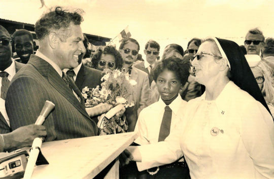 Minister Leo Chance being greeted by Sister Agatha on the opening of the pier named after him on November 8th, 1972. Will Johnson leader of the WIPM government (in dark glasses) looking on.