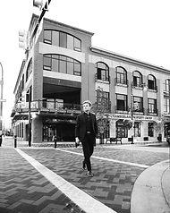 Man Walking On Crosswalk By Penticton Apartments Lofts On Main