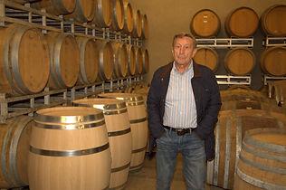 Person in einer Weinkllerei im Piemont mit vielen Weinfässern