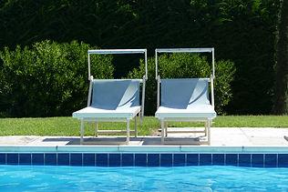 Zwei Liegestühle am Pool