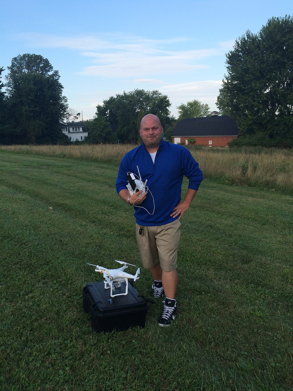 Tom Wasinski holding remote control gear and standing next to his drone.