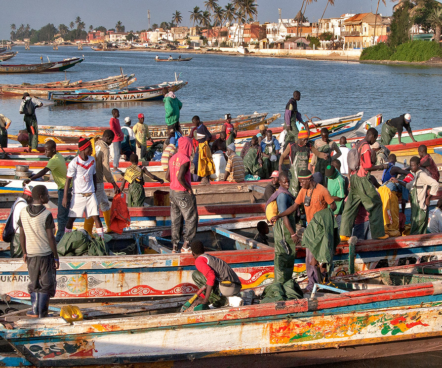 """The name 'Senegal' comes from the Wolof language, 'Sunuu Gaal', meaning """"our Boat"""". Senegal is the westernmost country on the mainland of the Old World, known as the 'Gateway to Africa', with its capital in Dakar. Fishing, phosphate mines, fertilizer, building materials, petroleum and ship constuction and repair are the primary industries. Agriculture includes peanuts, sugarcane, cotton, green beans, tomatoes, melons, and mangoes. Composed of many ethnicities, Senegal is predominantly Sunni Muslim with Sufi and animist influences. Many native languages are spoken, though French is the official language. Throughout the region the tradition of storytelling has kept West African history alive for thousands of years through words and music."""