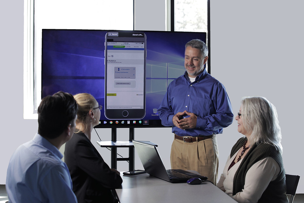 Man presenting a mobile app design to stakeholders using a large screen monitor in a conference room.
