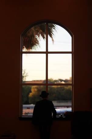 Man standing in tefilin in front of window