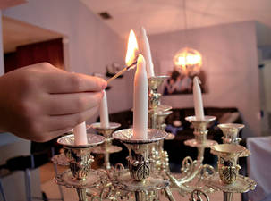Hand lighting Shabbos candles with match