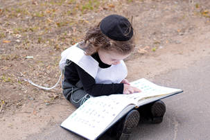 Upsherin boy sitting and reading the aleph beis