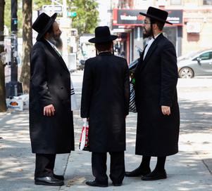 Three Hasidic Jews in a traditional long, dark jackets and hats, Brooklyn, New York