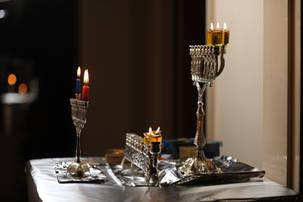 Three menorahs on the table lit on Chanukah