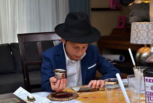 Bar mitzvah boy holding a kiddush cup benching