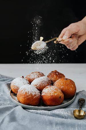 Sprinkling powdered sugar on top of donuts