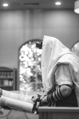 Man wearing talis reading from the Sefer Torah