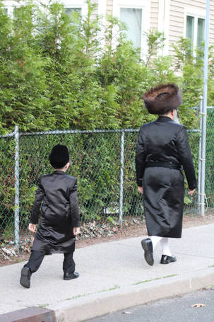 Chassidishe man and boy walking up the block