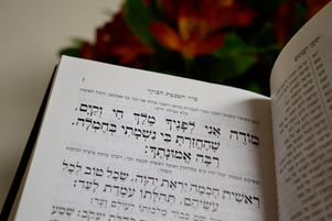 Siddur open to Modeh Ani in front of flowers