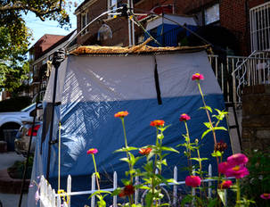 Small Sukkah with flowers in front and another small sukkah behind